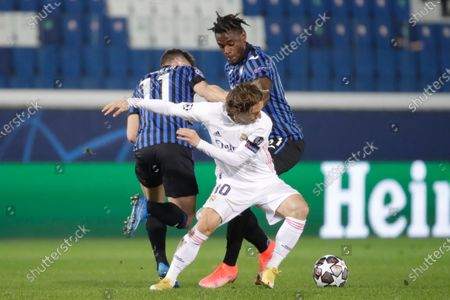 Real Madrid's Luka Modric, center, is challenged by Atalanta's Duvan Zapata, right, and Atalanta's Remo Freuler during the Champions League, round of 16, first leg soccer match between Atlanta and Real Madrid, at the Gewiss Stadium in Bergamo