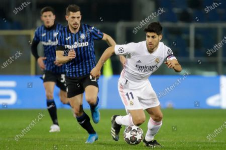 Real Madrid's Marco Asensio, right, is challenged by Atalanta's Remo Freuler during the Champions League, round of 16, first leg soccer match between Atlanta and Real Madrid, at the Gewiss Stadium in Bergamo