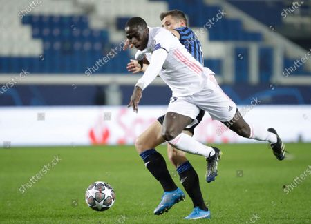 Real Madrid's Ferland Mendy, foreground, is fouled by Atalanta's Remo Freuler, which results in Freuler being shown a red card during the Champions League, round of 16, first leg soccer match between Atlanta and Real Madrid, at the Gewiss Stadium in Bergamo