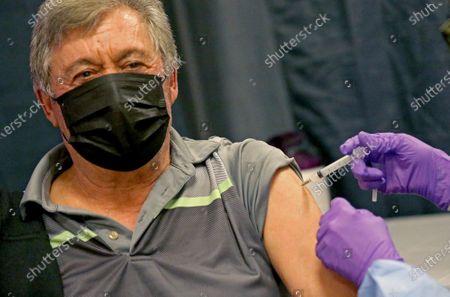 Antonio Loffa of Natick gets his COVID-19 vaccine at a mass vaccination site at the Natick Mall, in Natick, Mass