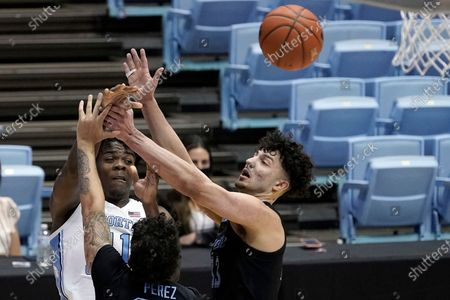 North Carolina forward Day'Ron Sharpe (11) passes the ball past Marquette forward Dawson Garcia (33) and guard Jose Perez during the first half of an NCAA college basketball game in Chapel Hill, N.C