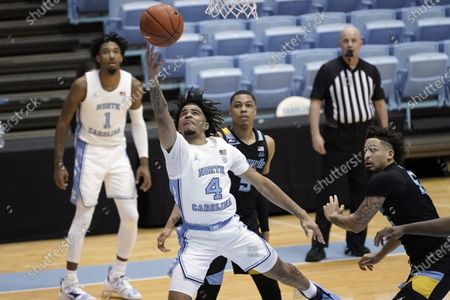 North Carolina guard R.J. Davis (4) drives to the basket while Marquette guards Greg Elliott (5) and Jose Perez, right, watch during the first half of an NCAA college basketball game in Chapel Hill, N.C