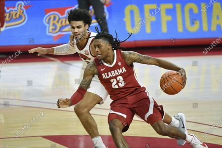 Alabama guard John Petty Jr. (23) tries to drive past Arkansas forward Justin Smith (0) during the second half of an NCAA college basketball game in Fayetteville, Ark