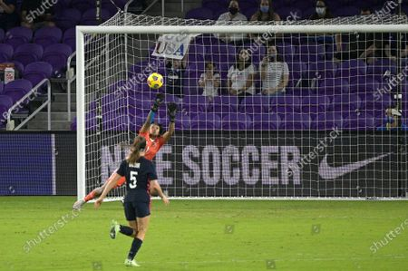 Stock Image of Argentina goalkeeper Solana Pereyra (1) makes a save as United States defender Kelley O'Hara (5) watches during the first half of a SheBelieves Cup women's soccer match, in Orlando, Fla