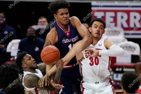 UNLV's David Jenkins Jr., left, Fresno State's Orlando Robinson, center, and UNLV's Devin Tillis compete for a rebound during the first half of an NCAA college basketball game, in Las Vegas