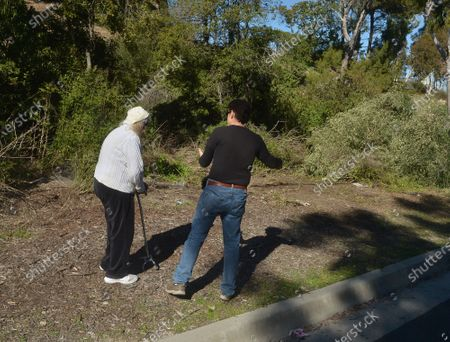 Local residents Janet Engelman, 82, and her son Alexander are seen in the area where golf legend Tiger Woods rolled his car after crossing a median in Rolling Hills Estates, California on Wednesday, February 24, 2021. Experts say Tiger Woods has a long way to go in his recovery process from the broken leg, ankle and foot injuries he sustained in a car crash Tuesday in Southern California