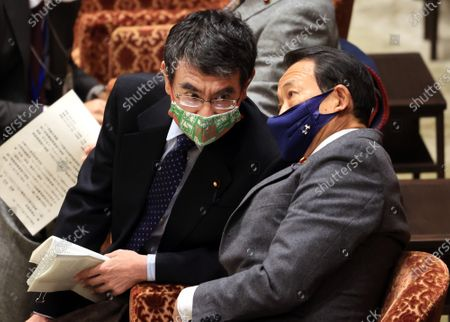Japanese Administrative Reform Minister Taro Kono (L) listens to Finance Minister Taro Aso (R) before starting Lower House's budget committee session at the National Diet in Tokyo on Thursday, February 25, 2021. Prime Minister Yoshihide Suga's son Seigo provided dinners and gifts for communications ministry bureaucrats in violations of the national public service ethics law.