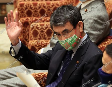 Japanese Administrative Reform Minister Taro Kono raises his hand to answer a question at Lower House's budget committee session at the National Diet in Tokyo on Thursday, February 25, 2021. Prime Minister Yoshihide Suga's son Seigo provided dinners and gifts for communications ministry bureaucrats in violations of the national public service ethics law.
