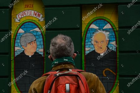 A man looks at images of Father Ted and Father Jack seen in windows of a closed Pub in Dublin city center during Level 5 Covid-19  lockdown. On Wednesday, February 24, 2021, in Dublin, Ireland. (Photo by Artur Widak/NurPhoto)