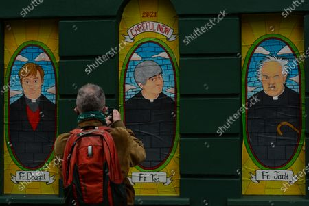 Stock Picture of A man takes pictures of Father Dougal, Father Ted and Father Jack images seen in windows of a closed Pub in Dublin city center during Level 5 Covid-19  lockdown. On Wednesday, February 24, 2021, in Dublin, Ireland. (Photo by Artur Widak/NurPhoto)
