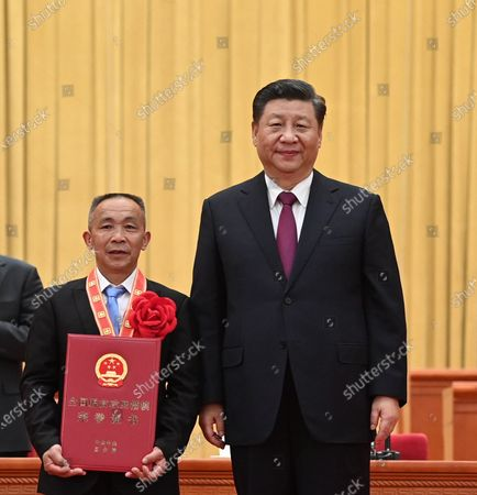 Chinese President Xi Jinping, also general secretary of the Communist Party of China Central Committee and chairman of the Central Military Commission, presents an award to Mao Xianglin, a role model in China's poverty alleviation fight during a grand gathering to mark the nation's poverty alleviation accomplishments and honor model poverty fighters at the Great Hall of the People in Beijing, capital of China, Feb. 25, 2021.