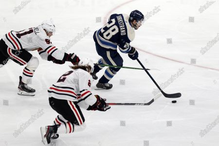 Columbus Blue Jackets forward Oliver Bjorkstrand, right, controls the puck against Chicago Blackhawks defenseman Ian Mitchell, left, and defenseman Duncan Keith during an NHL hockey game in Columbus, Ohio, . The Blackhawks won 6-5 in a shootout