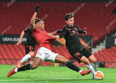 Manchester United's Anthony Martial (L) in action against Real Sociedad's Martin Zubimendi (R) during the UEFA Europa League round of 32, second leg soccer match between Manchester United and Real Sociedad in Manchester, Britain, 25 February 2021.