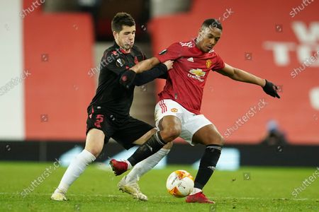 Real Sociedad's Igor Zubeldia vies for the ball with Manchester United's Anthony Martial, right, during the Europa League round of 32, second leg, soccer match between Manchester United and Real Sociedad at Old Trafford in Manchester, England