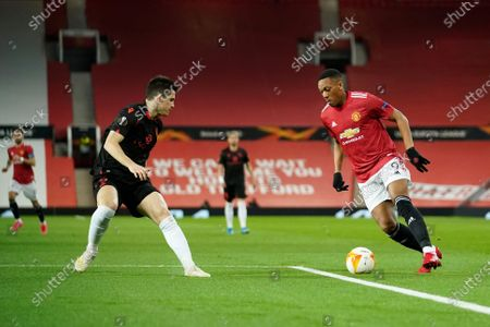 Manchester United's Anthony Martial, right, runs with the ball at Real Sociedad's Igor Zubeldia during the Europa League round of 32, second leg, soccer match between Manchester United and Real Sociedad at Old Trafford in Manchester, England