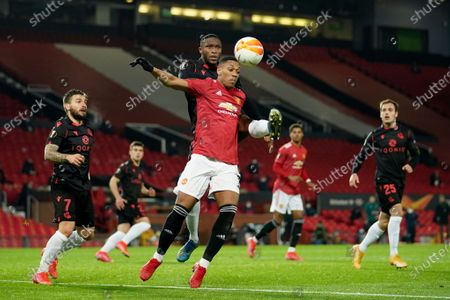 Real Sociedad's Modibo Sagnan fights for the ball with Manchester United's Anthony Martial, foreground, during the Europa League round of 32, second leg, soccer match between Manchester United and Real Sociedad at Old Trafford in Manchester, England