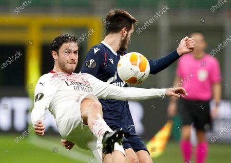 Stock Image of Milan's Davide Calabria, left, challenges for the ball with Red Star's Mirko Ivanic during the Europa League round of 32 second leg soccer match between AC Milan and Red Star Belgrade at the San Siro Stadium, in Milan, Italy