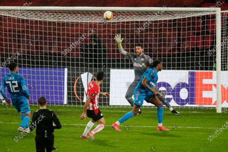 PSV's Eran Zahavi, center, fails to score as Olympiacos' goalkeeper Jose Sa, rear, lets the ball go over during the Europa League round of 32 second leg soccer match between PSV and Olympiacos at the Philips stadium in Eindhoven, Netherlands