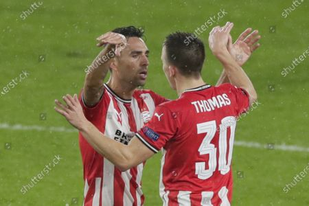 PSV's Ryan Thomas, right, celebrates with PSV's Eran Zahavi who scored his side's first goal during the Europa League round of 32 second leg soccer match between PSV and Olympiacos at the Philips stadium in Eindhoven, Netherlands