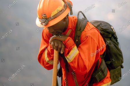 """An inmate firefighter rests during a break from battling the River Fire in Salinas, Calif. California could change its constitutional ban on slavery to remove the words """"unless for the punishment of crime,"""" further reducing the state's already faltering dependence on thousands of inmate firefighters, under a proposed amendment backed, by local officials and actor-activist Danny Glover"""