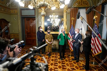 Stock Image of Former Michigan Governor Jennifer Granholm is sworn in as Energy Secretary by Vice President Kamala Harris, as her husband Dan Mulhern holds the Bible, in the Eisenhower Executive Office Building in the White House complex, in Washington. Granholm's daughter Cecelia Mulhern and son-in-law Damian Roberto Mendieta, look on