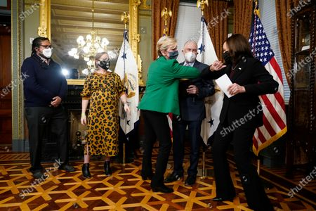 Former Michigan Governor Jennifer Granholm elbow bumps Vice President Kamala Harris, after being sworn in by Harris as Energy Secretary, as her husband Dan Mulhern looks, in the Eisenhower Executive Office Building in the White House complex, in Washington. Granholm's daughter Cecelia Mulhern and son-in-law Damian Roberto Mendieta, look, left