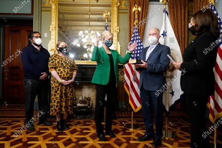 Former Michigan Governor Jennifer Granholm reacts after being sworn in as Energy Secretary by Vice President Kamala Harris, as her husband Dan Mulhern holds the Bible, in the Eisenhower Executive Office Building in the White House complex, in Washington. Granholm's daughter Cecelia Mulhern and son-in-law Damian Roberto Mendieta, look on