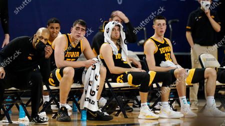 Iowa center Luka Garza (55), Iowa forward Jack Nunge (2), and guards Jordan Bohannon, center, and Joe Wieskamp (10) sit on the bench during the closing minutes of an NCAA college basketball game against Michigan, in Ann Arbor, Mich