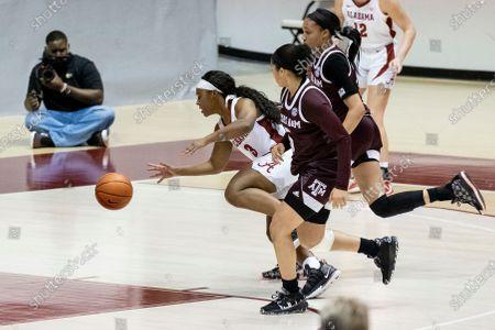 Alabama guard Jordan Lewis (3) dribbles though a double-team of Texas A&M guard Jordan Nixon (5) and forward N'dea Jones (31) during the first half of an NCAA college basketball game, in Tuscaloosa, Ala