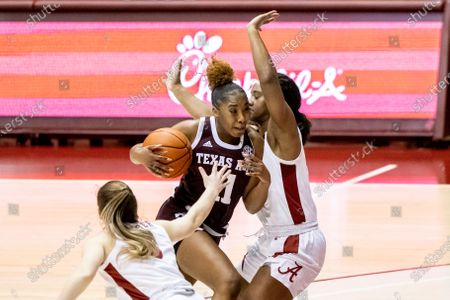 Texas A&M guard Kayla Wells (11) works between Alabama guards Hannah Barber, left, and Jordan Lewis, right, during the first half of an NCAA college basketball game, in Tuscaloosa, Ala