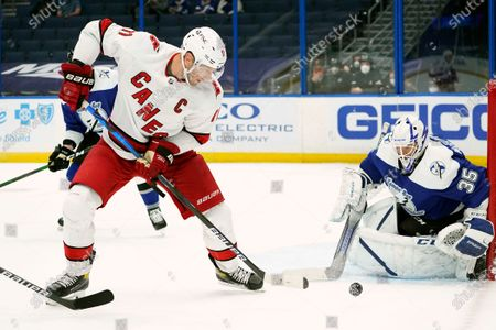 Carolina Hurricanes center Jordan Staal (11) gets off a shot on Tampa Bay Lightning goaltender Curtis McElhinney (35) during the first period of an NHL hockey game, in Tampa, Fla