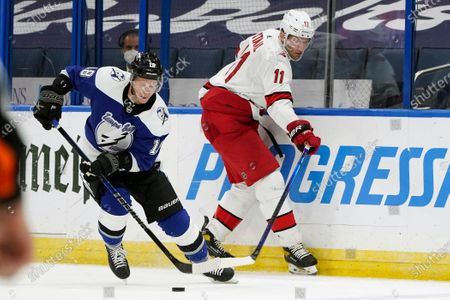 Tampa Bay Lightning left wing Ondrej Palat (18) steals the puck from Carolina Hurricanes center Jordan Staal (11) during the first period of an NHL hockey game, in Tampa, Fla
