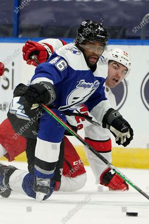Tampa Bay Lightning center Gemel Smith (46) pushes the puck away fromt Carolina Hurricanes left wing Jordan Martinook (48) during the second period of an NHL hockey game, in Tampa, Fla