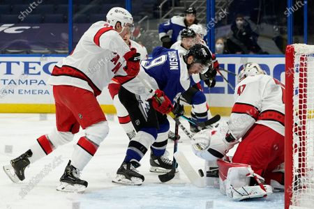 Tampa Bay Lightning center Tyler Johnson (9) and Carolina Hurricanes defenseman Jake Bean (24) battle for a loose puck in front of goaltender James Reimer (47) during the second period of an NHL hockey game, in Tampa, Fla