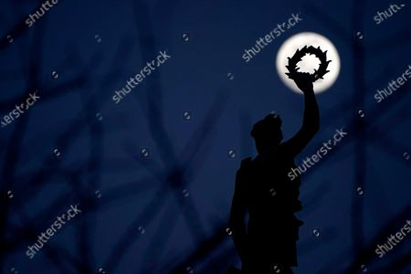 Stock Picture of Waxing moon is seen behind trees and and a statue atop the Peggy Stewart Monument, in Baltimore, Md. The monument honors the Peggy Stewart, a brigantine ship that was burned when it arrived at the port of Annapolis in October 1774, with a cargo of tea, which violated a boycott on a highly controversial tax imposed by Britain