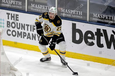 Stock Photo of Boston Bruins defenseman John Moore (27) skates with the puck against the New York Islanders during the first period of an NHL hockey game, in Uniondale, N.Y
