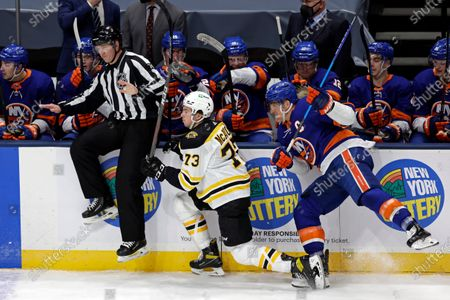 Boston Bruins defenseman Charlie McAvoy (73) avoids a check by New York Islanders center Anders Lee during the first period of an NHL hockey game, in Uniondale, N.Y