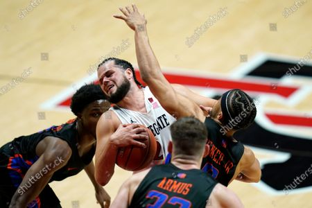 Stock Image of Boise State guard Marcus Shaver Jr., right, fouls San Diego State guard Jordan Schakel, center, during the first half of an NCAA college basketball game, in San Diego