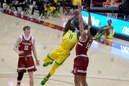 Oregon guard Amauri Hardy (11) shoots between Stanford forwards Spencer Jones (14) and Max Murrell (10) during the first half of an NCAA college basketball game in Stanford, Calif