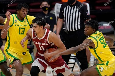 Stanford forward Jaiden Delaire (11) drives between Oregon forwards Chandler Lawson (13) and Eric Williams Jr. (50) during the first half of an NCAA college basketball game in Stanford, Calif