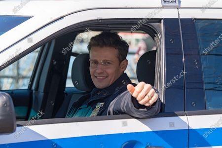 """Will Estes is seen on a film production trailer during the filming of the television show """"Blue Bloods"""" season eleven in Astoria Park in New York City."""