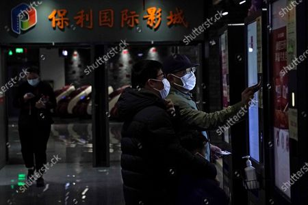 Stock Photo of People wearing face masks to help curb the spread of the coronavirus collect their movie tickets at Poly Cinema in Beijing on . With coronavirus well under control in China and cinemas running at half capacity, moviegoers are smashing China's box office records, setting a new high mark for ticket sales in February, with domestic productions far outpacing their Hollywood competitors