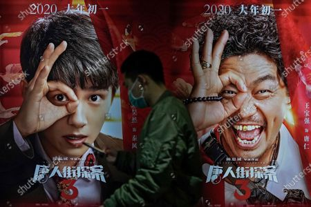 Stock Image of Man wearing a face mask to help curb the spread of the coronavirus walks by a movie poster at Poly Cinema in Beijing on . With coronavirus well under control in China and cinemas running at half capacity, moviegoers are smashing China's box office records, setting a new high mark for ticket sales in February, with domestic productions far outpacing their Hollywood competitors