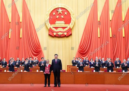 Stock Picture of Chinese President Xi Jinping, also general secretary of the Communist Party of China Central Committee and chairman of the Central Military Commission, presents an award to Mao Xianglin, a role model in China's poverty alleviation fight, during a grand gathering to mark the nation's poverty alleviation accomplishments and honor model poverty fighters at the Great Hall of the People in Beijing, capital of China, Feb. 25, 2021.