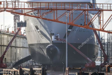 Workers at the bow of a built mega sits in a floating dock at the Lloyd-Werft shipyards in Bremerhaven, northern Germany, 26 February 2021. According to a report of German float Magazin, the 140 meters long ship is the Solaris, an expedition yacht owned by Russian billionaire Roman Abramovich. As the Llyod shipyards could be closed in the near future due to financial problems, the ship might be its last mega yacht.
