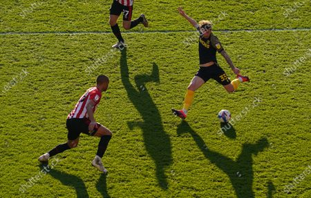 Josh Tymon of Stoke City gets a shot on goal near Winston Reid of Brentford
