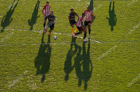 The long shadows of Nick Powell and Jacob Brown, and Vitaly Janelt, Ethan Pinnock and Winston Reid of Brentford