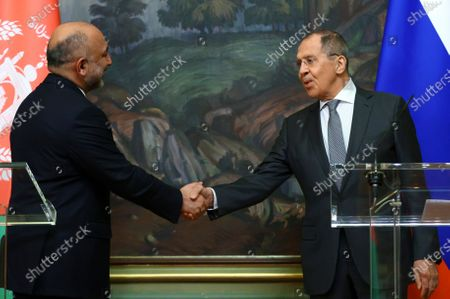 Russian Foreign Minister Sergei Lavrov (R) shakes hands with Afghanistan's Foreign Minister Mohammad Hanif Atmar (L) at the press conference during their meeting in Moscow, Russia, 26 February 2021.