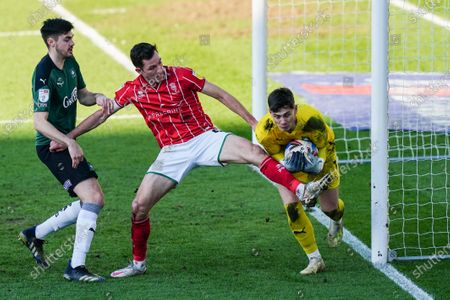 Goalkeeper Michael Cooper of Plymouth Argyle gathers the ball to deny Tom Hopper of Lincoln City at close range