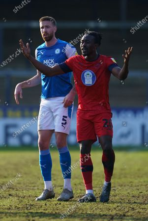 Mark Beevers of Peterborough United (5) looks on as Joe Dodoo of Wigan Athletic (20) reacts after being fouled